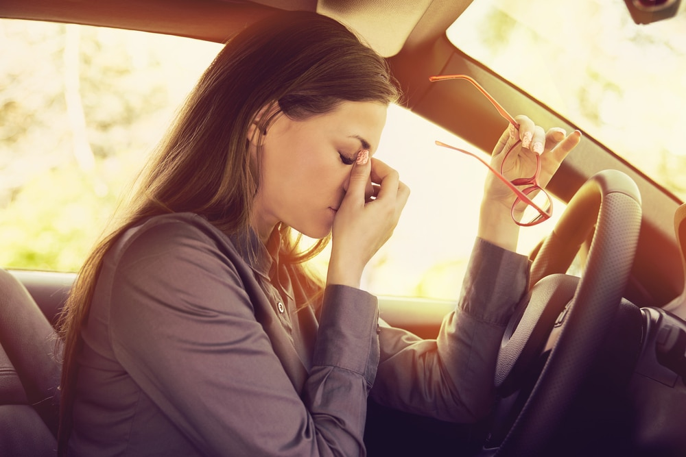 woman-holding-face-suffering-low-energy-in-car (641921188)